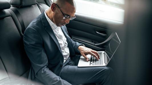 Businessman using laptop sitting in car