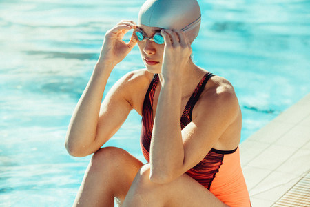 Woman in swimming gear sitting on the edge of the pool
