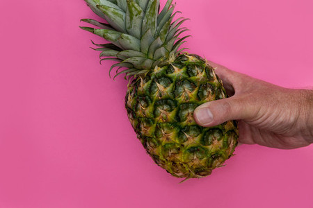 Pineapple fruit held in hand on pink background minimal summer f