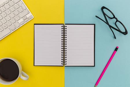 Notebook computer keyboard on minimal yellow background