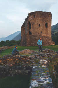 Tourists looking at sunset from Dolbadarn Castle Snowdonia National Park in North Wales