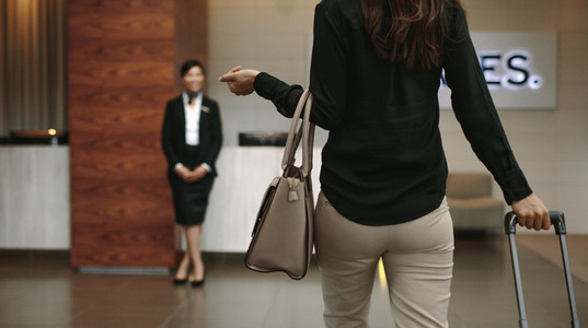 Business woman arriving at hotel with luggage