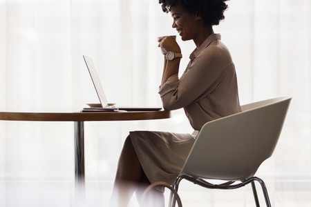 Office worker having coffee and looking at laptop