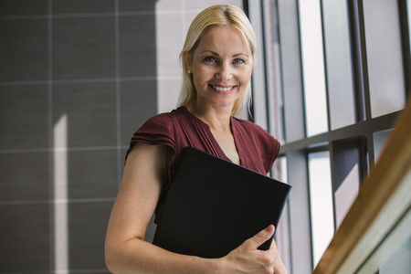 Smiling businesswoman with a file in office