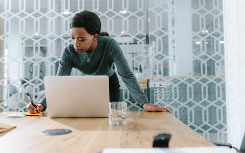 Businesswoman in boardroom making notes for meeting