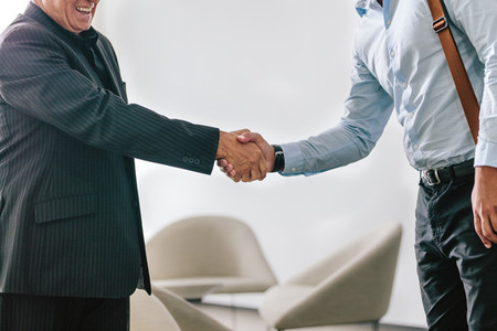 Business men shaking hands in office lobby