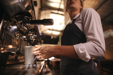 Barista making coffee on coffee maker machine