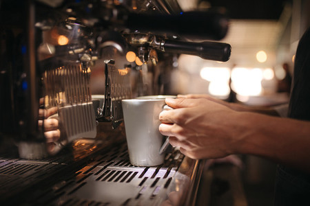 Female cafe worker preparing coffee in machine