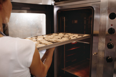 Female baker baking rolls