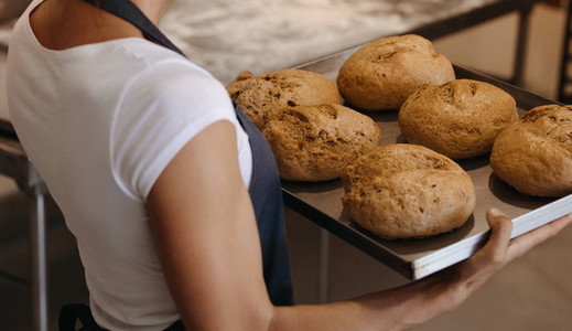 Woman with a tray freshly baked bread