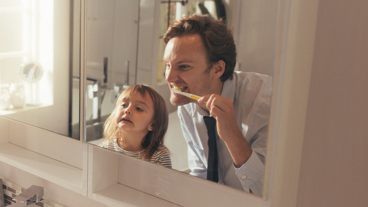 Father teaching daughter how to brush teeth