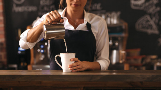 Female barista making a cup of coffee