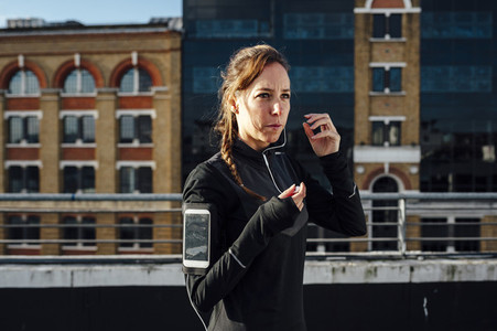 Blonde woman using smart phone armband with headphones while exercising in urban scenery at sunrise