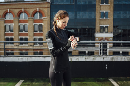 Blonde woman checks activity at smart watch after outdoor urban running exercise