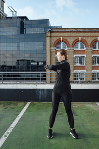 Blonde woman stretching arms before urban workout at rooftop in the morning