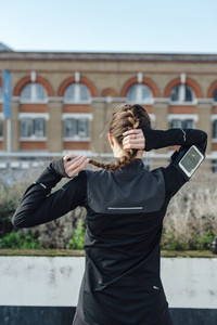 Back view of a running woman tying up her ponytail before workout at urban scenery