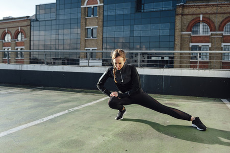 Blonde woman stretching legs before urban workout at rooftop in the morning