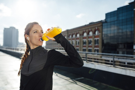 Blonde woman drinking isotonic beverage after urban workout at rooftop in the morning