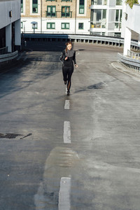 Blonde woman running on rooftop urban scenery at sunrise