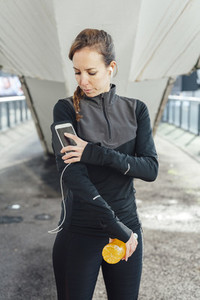 Blonde woman using smart phone armband while exercising in urban scenery at sunrise