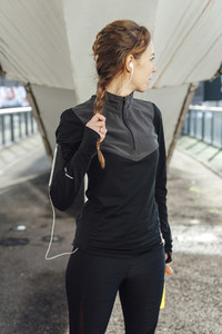 Portrait of a running woman tying up her ponytail after workout at urban scenery