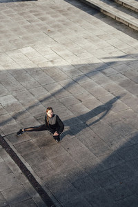 Blonde woman stretching legs before workout at urban scenery at sunset