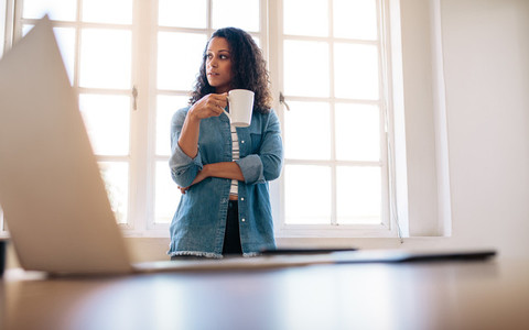 Businesswoman standing in office drinking coffee