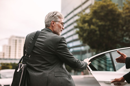 Mature businessman getting into a cab
