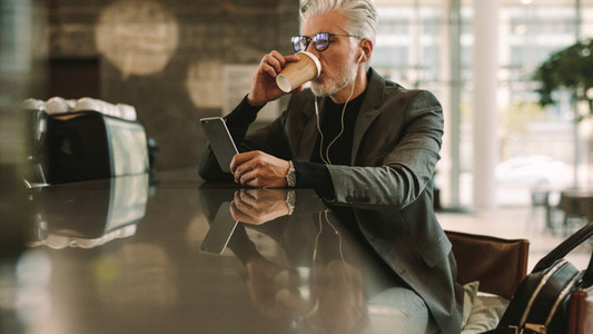 Businessman with phone drinking coffee