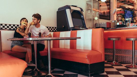 Romantic couple eating burgers at a diner