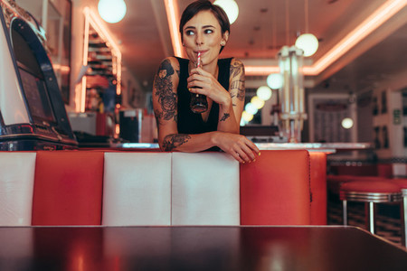 Woman at a diner drinking soft drink
