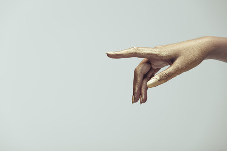 Golden painted hand pointing at copy space
