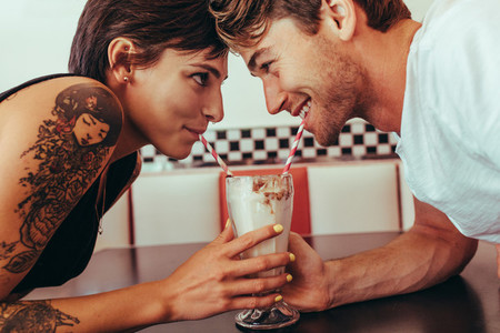Romantic couple sharing milk shake using straws from the same gl