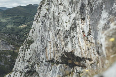 Rock climber male climbing on overhanging limestone mountain
