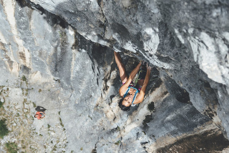 Marture strong woman climbing overhanging limestone wall
