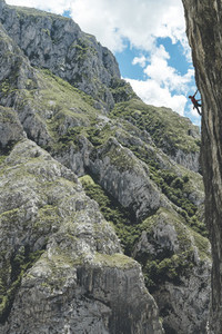 Silhouette of a climber climbing on a overhanging limestone wall