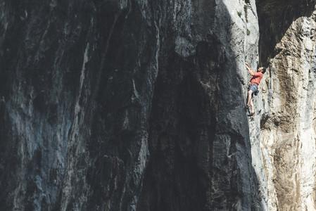 Male climber climbing limestone wall wearing a red t shirt