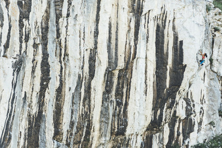 Matue strong woman climbing limestone wall with vertical lines as a cebra
