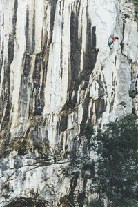 Mature strong woman climbing limestone wall with vertical lines as a cebra