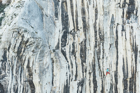 Male climber climbing limestone wall with vertical lines as a cebra