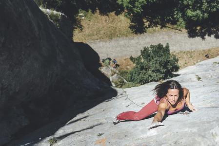 Attractive female climber climbing a vertical limestone wall