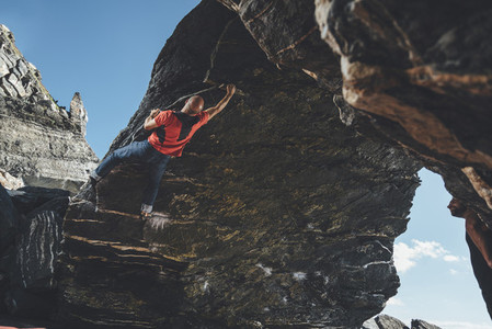 Mid aged climber climbing on a overhanging boulder problem