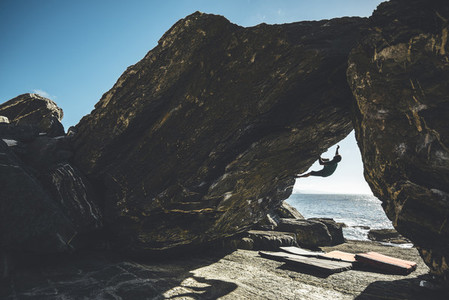Silhouette of a climber climbing in a overhanging boulder problen close to the sea