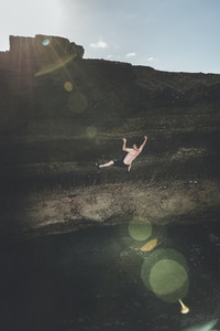 Climber climbing without ropes in a seacliff close to the water and lens flare