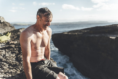Portrait of mature man climber resting in a rock