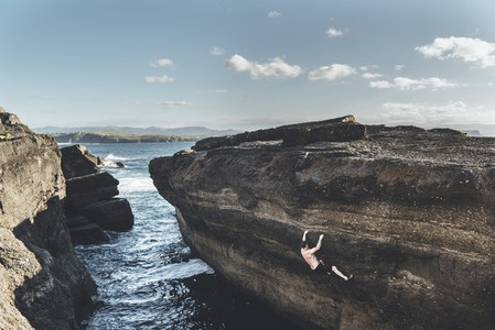 Climber climbing without ropes in a seacliff close to the water