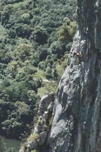 Mature woman climber climbing in a limestone cliff close to a dam