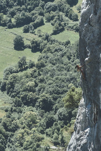 Mature woman climber climbing in a limestone cliff close to a dam