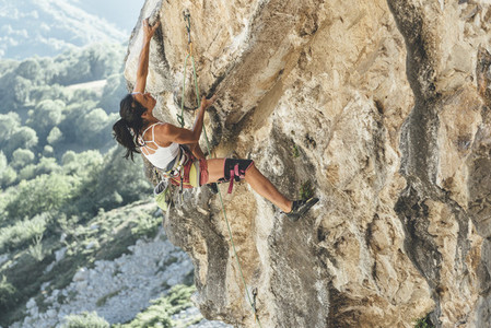 Mature strong woman climber climbing a overhanging limestone wall with tufas
