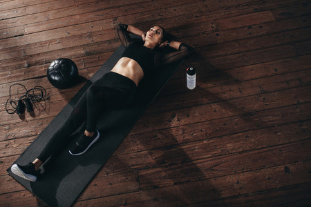 Fitness woman resting on floor exercising at gym